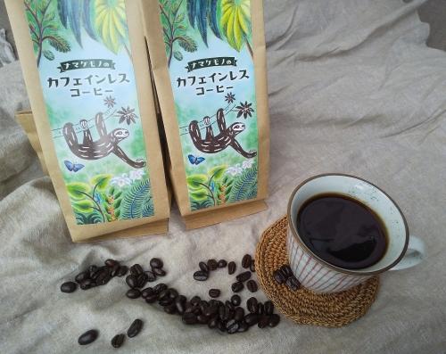 コーヒーの袋の横に、カップに入ったコーヒー、その下にコーヒー豆が散りばめられている様子